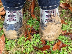 Muddy walking shoes in grass.