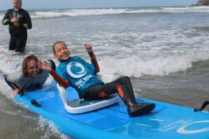 A girl with a disability riding a wave on a surfboard with instructor pushing the board.
