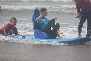 Instructors helping a guest surf at the Wave Project.