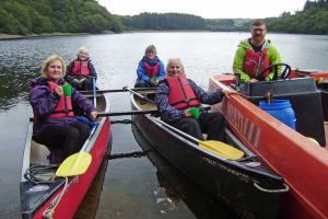 Four people sat in kayaks in a lake.