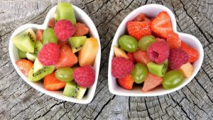 Two heart-shaped bowls full of colourful, chopped fruit.