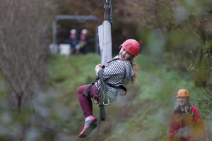 A girl smiling on the zipwire at Calvert Trust Exmoor.