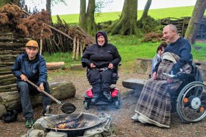 People sat around a campfire doing bush craft activities at the Calvert Trust Exmoor site.