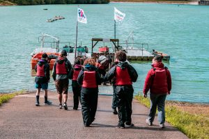 A group of guests wearing lifejackets heading over to the boats at the reservoir at the Calvert Trust Exmoor site.