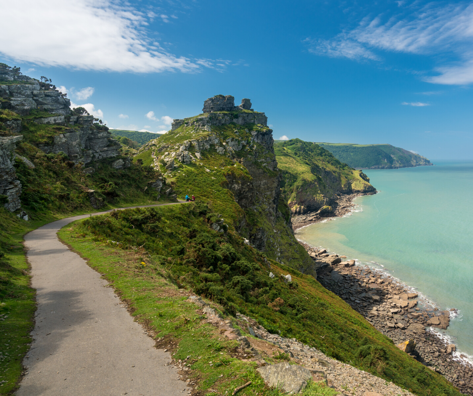View of a dramatic coastline and cliffs, blue sea and skies with a single path