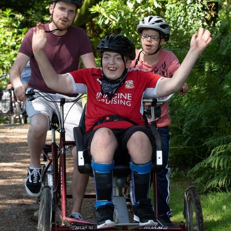 A teenager with disabilities sat in a seat on the front of a bike, with a man and another child peddling behind