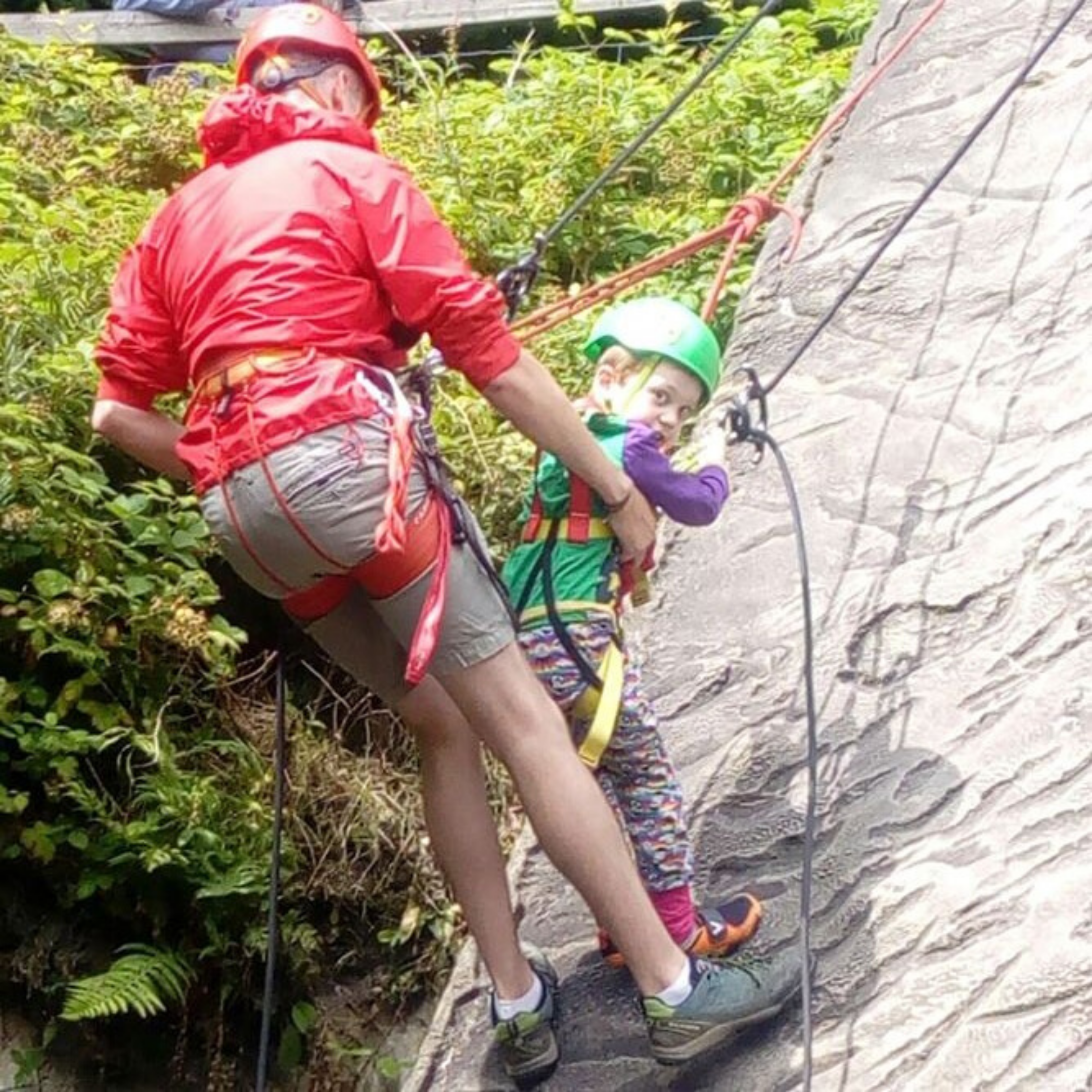A young boy and a man abseiling together
