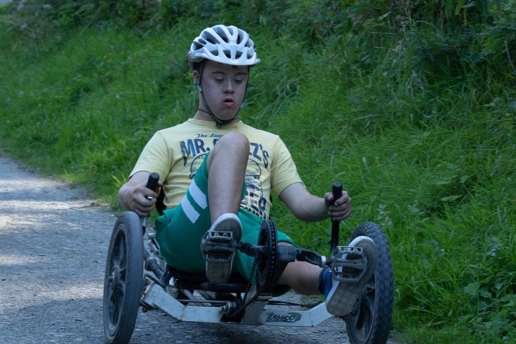 A young man wearing a helmet riding a recumbent bike