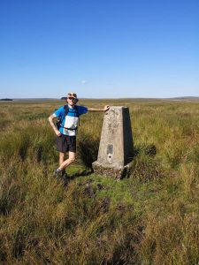 A man with a map next to a big stone marker on the moors of Exmoor