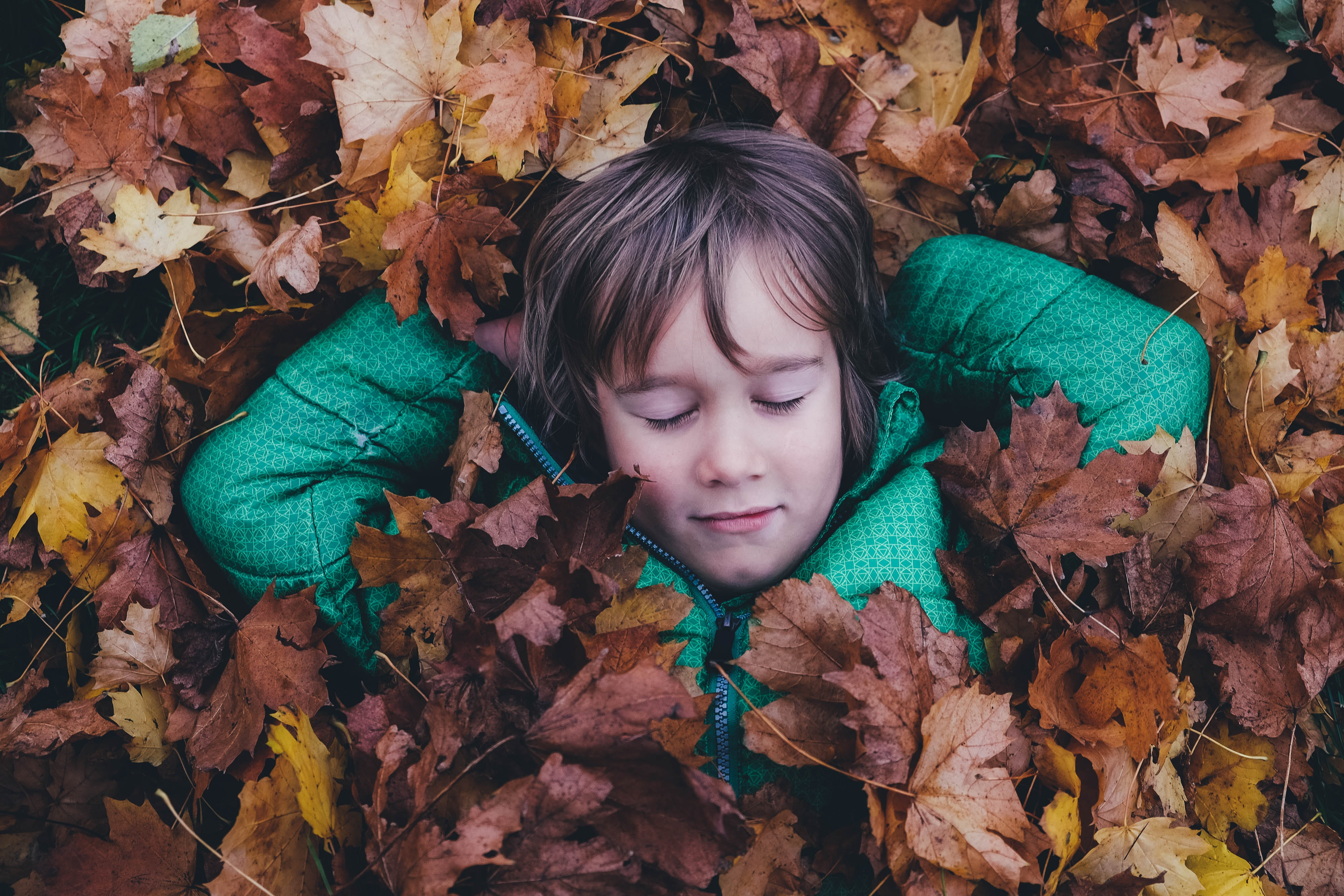 A child lying back in autumn leaves
