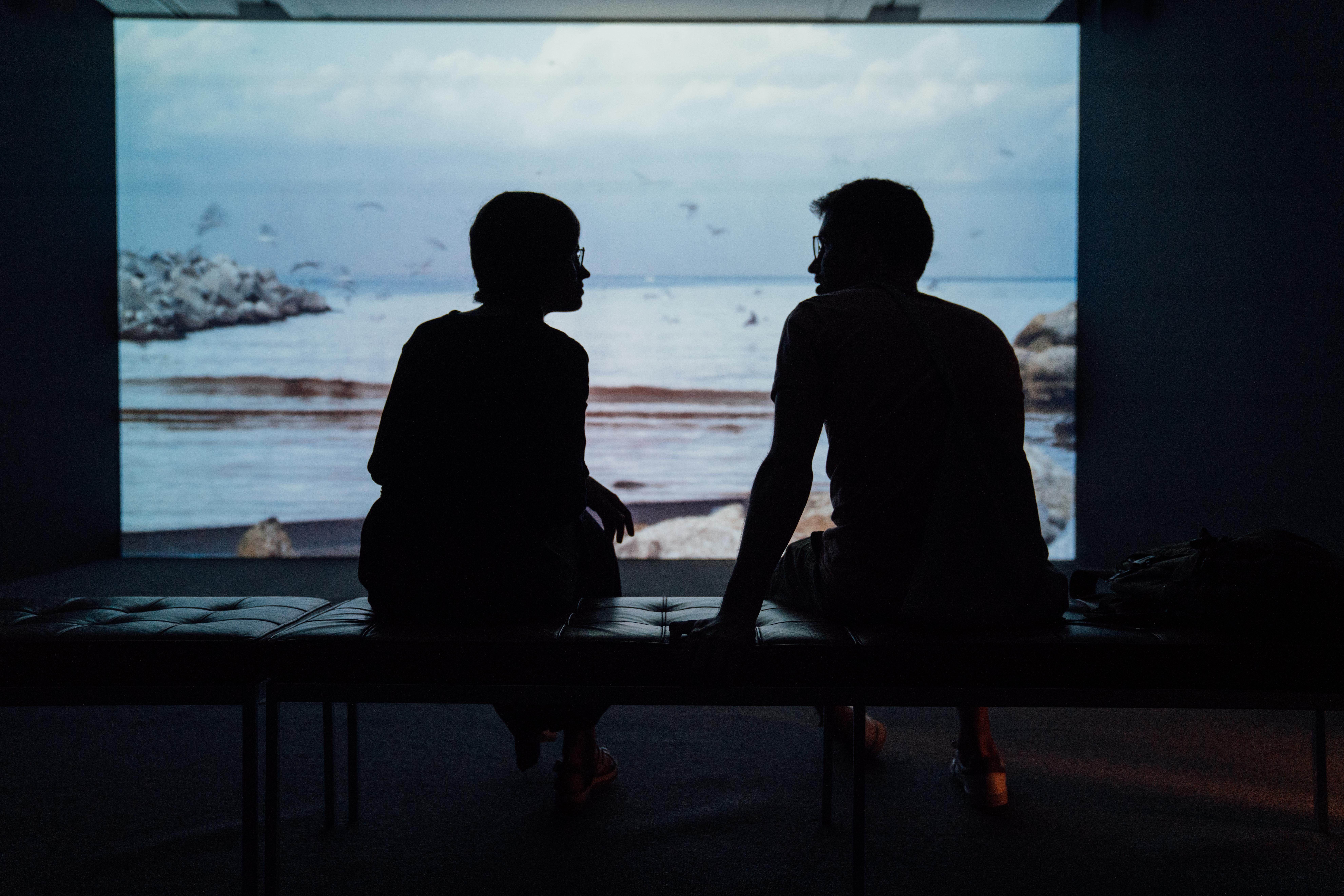 Two people talking in front of a projected video in a dark room