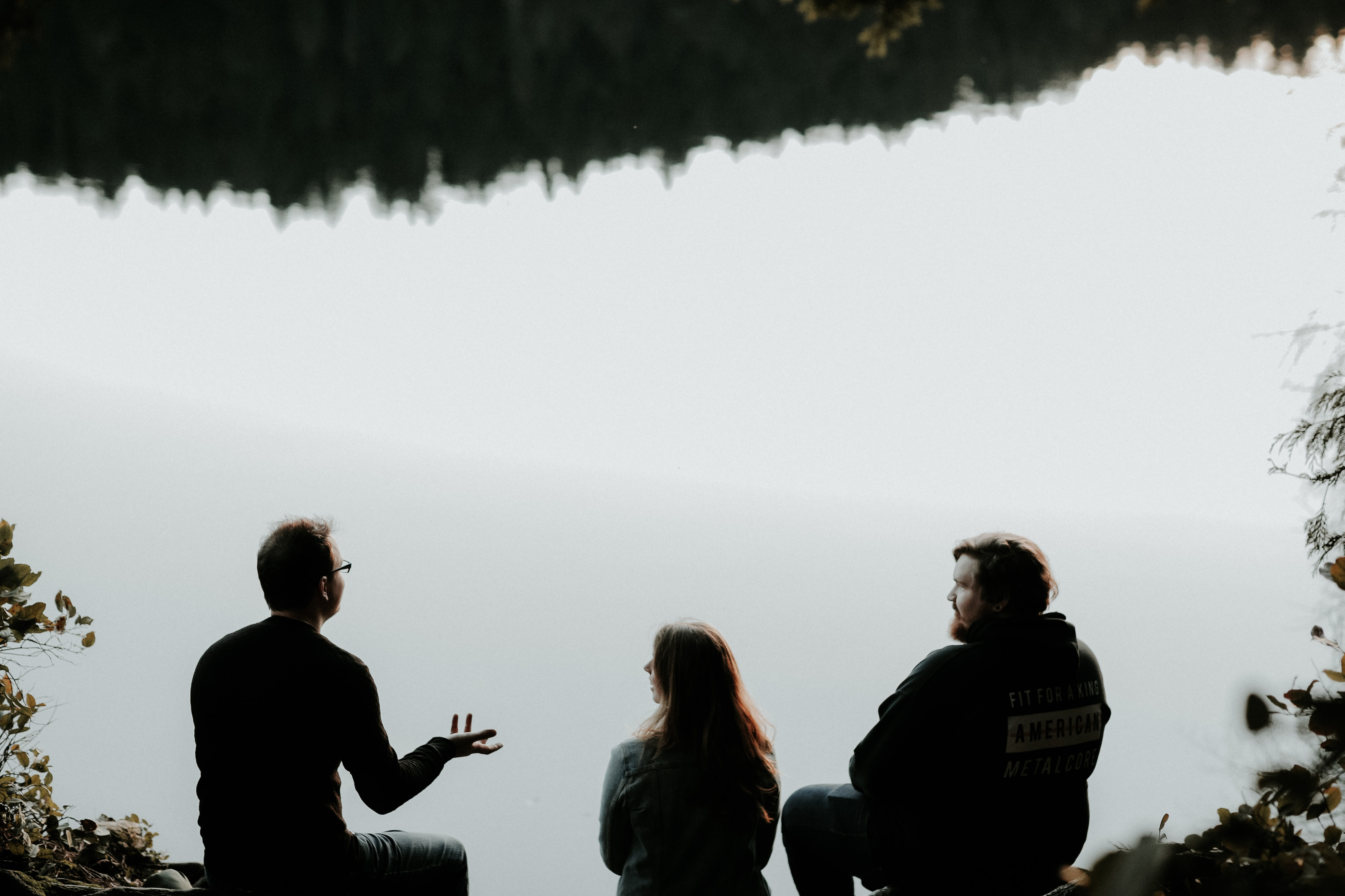 Three friends talking by a lake