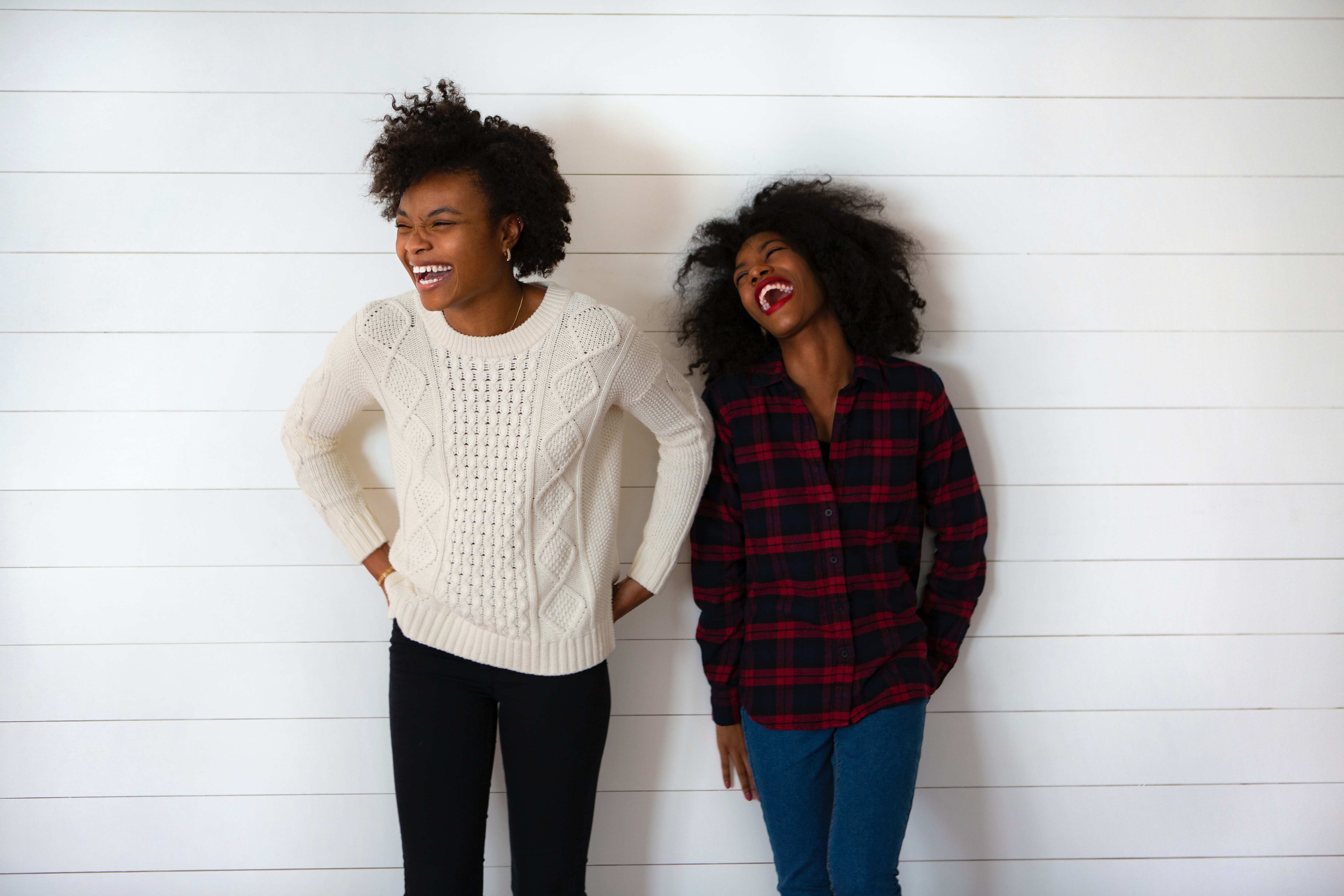 Two people leaning against a wall and laughing