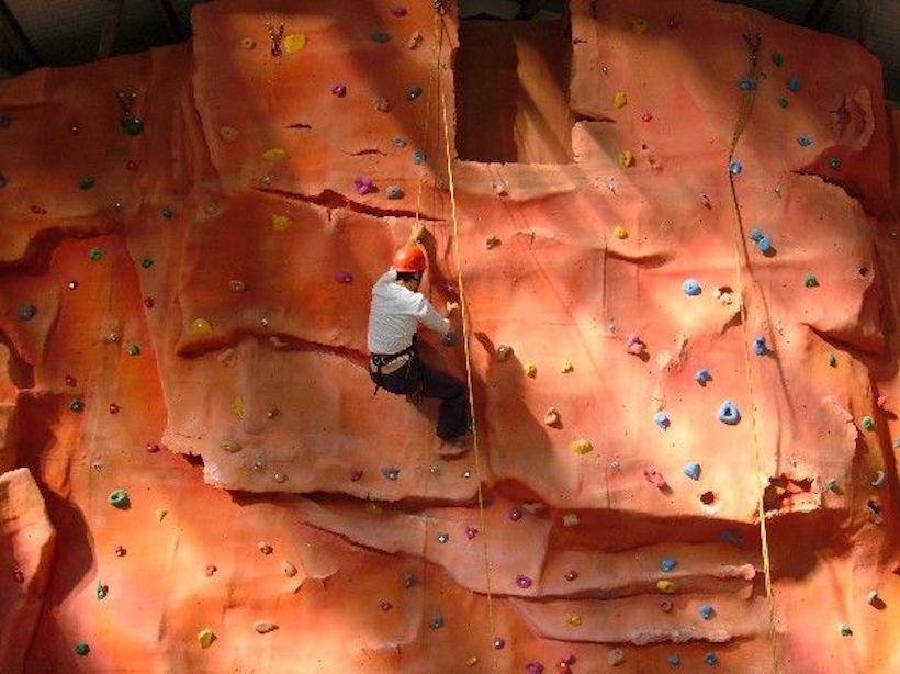 A guest on the climbing wall at Calvert Trust Exmoor