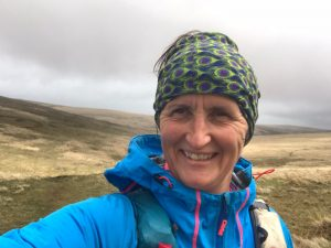 Kathy taking a selfie with open moor grassland and grey sky behind