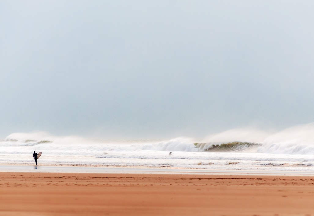 A surfer entering the sea at Croyde Bay