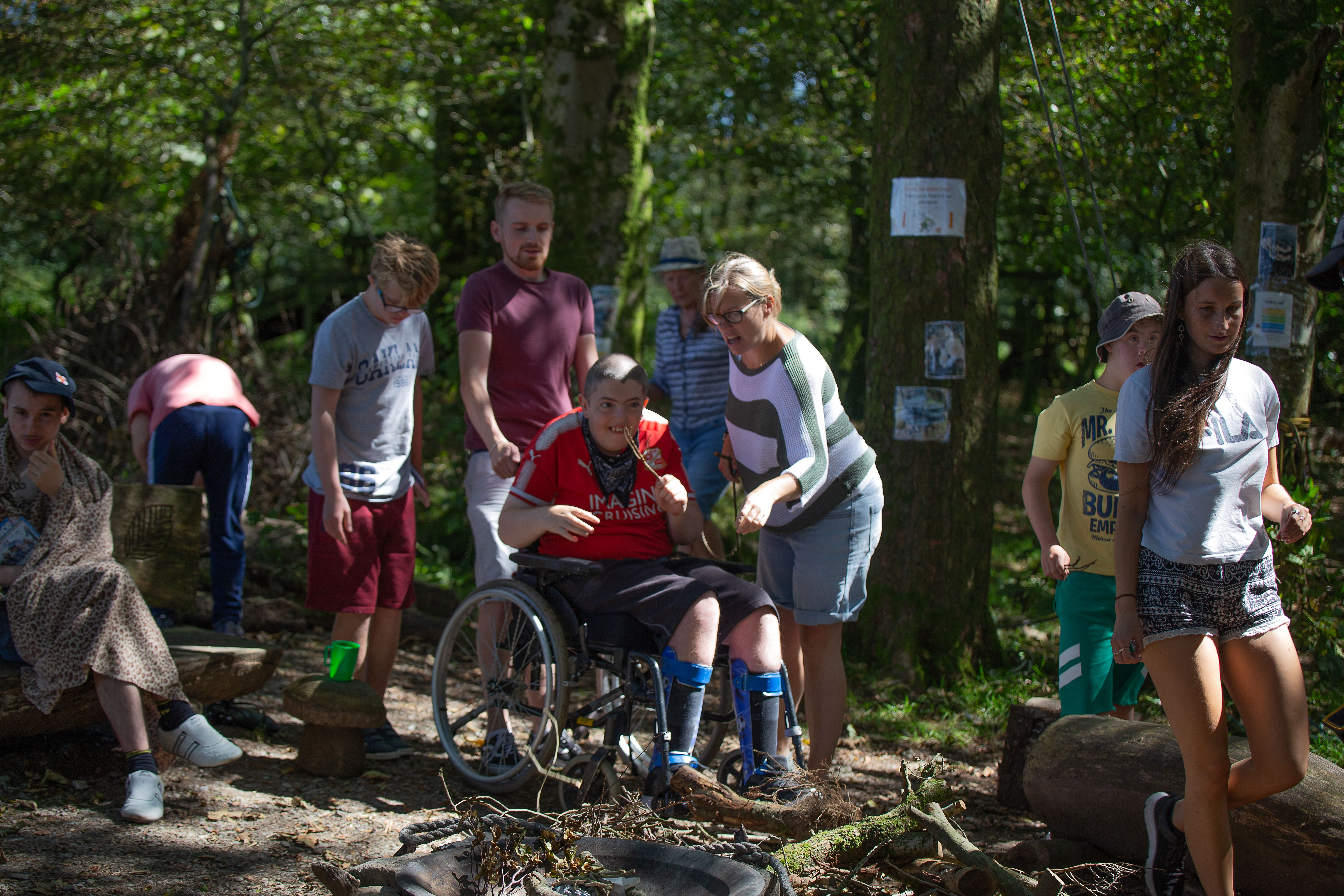 A wheelchair user and other guests in a forest