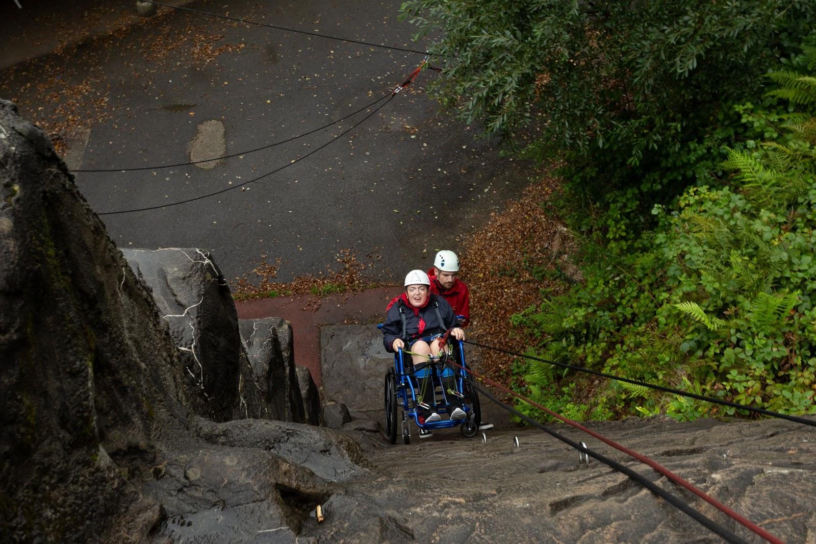 A Calvert Trust guest in a wheelchair on the abseiling wall