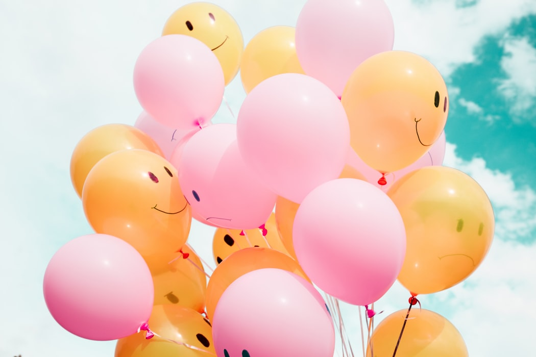 Pink and orange balloons with happy and sad faces on them