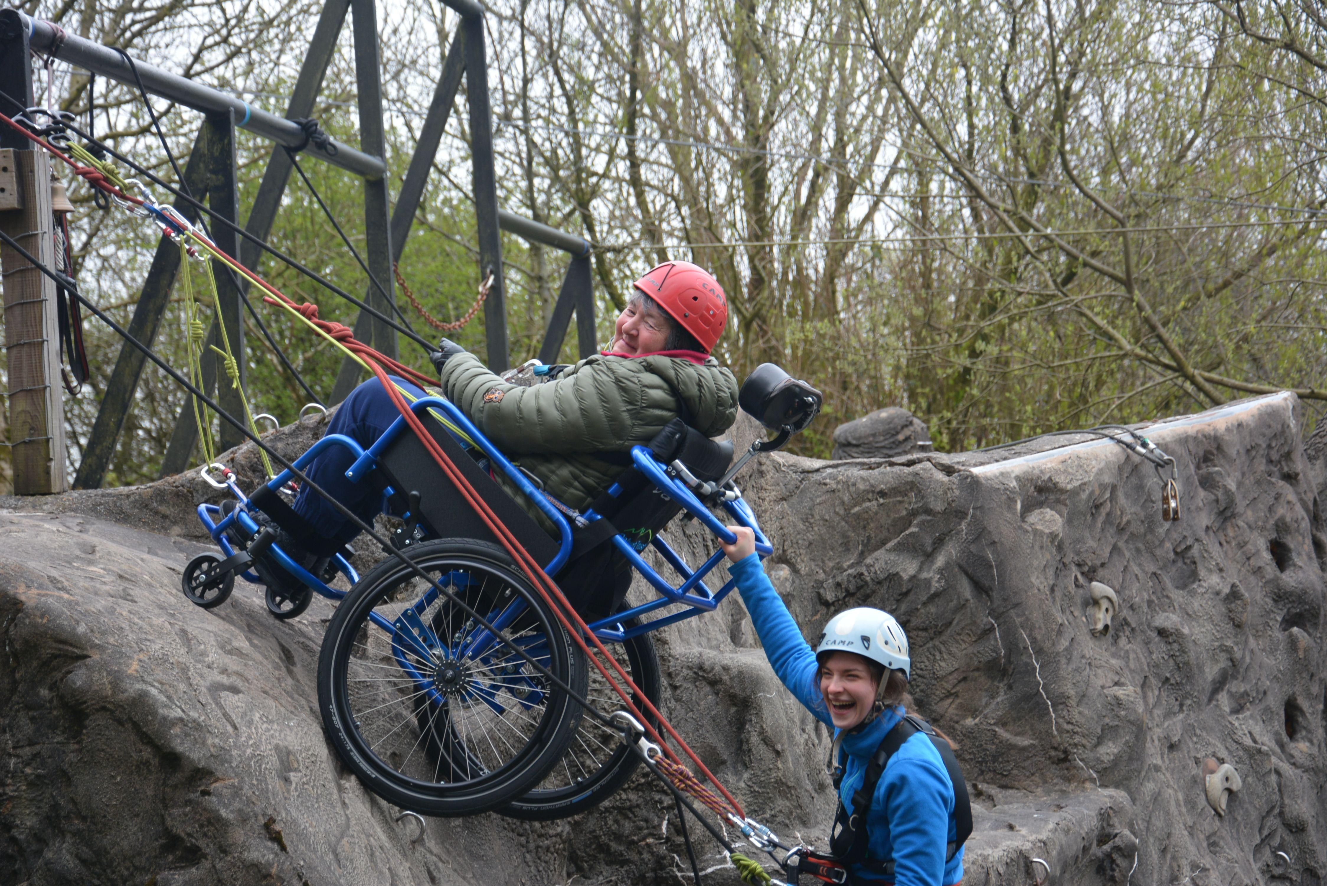 A woman in a wheelchair abseiling down a climbing wall