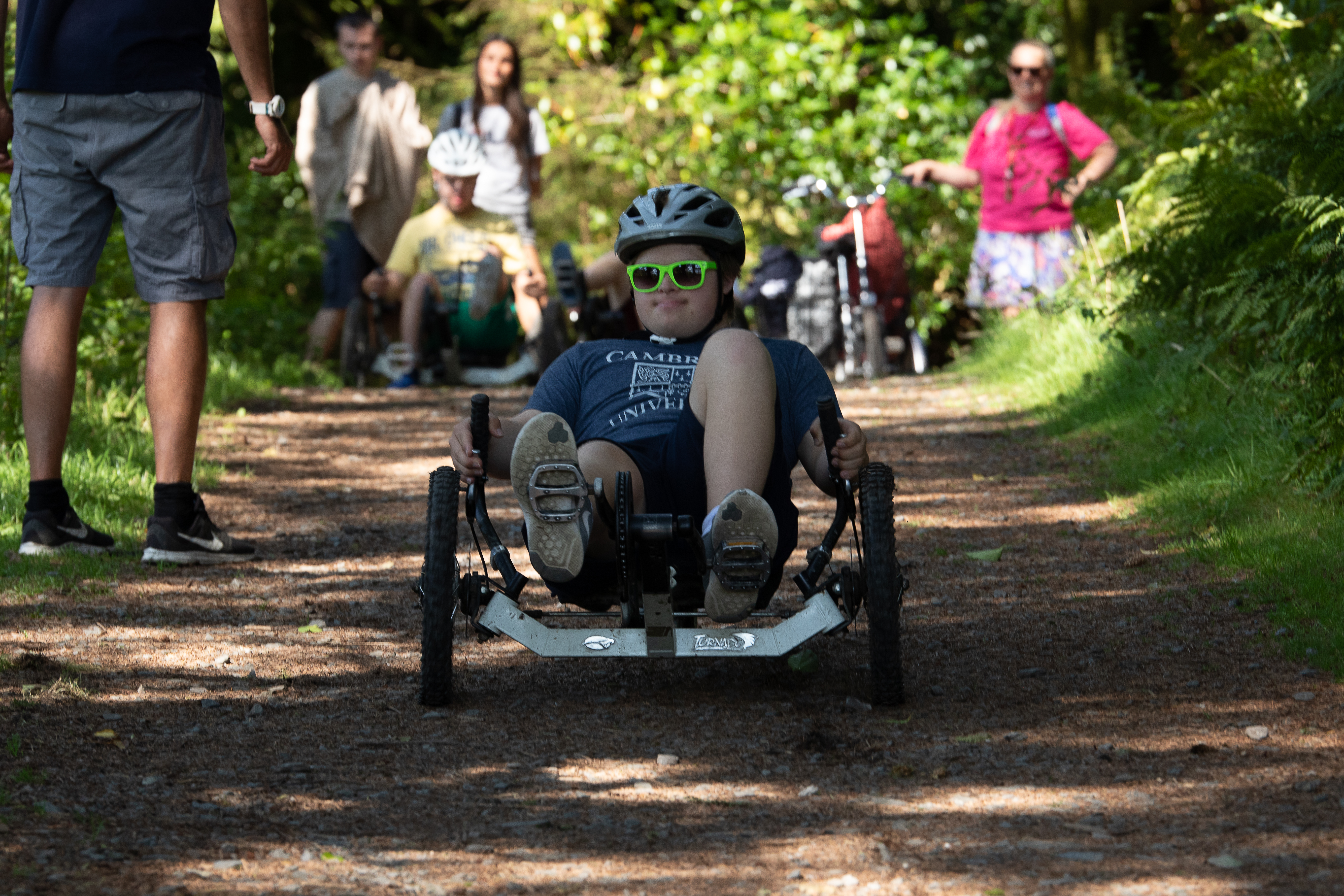 A guest on an accessible bike on a forest trail