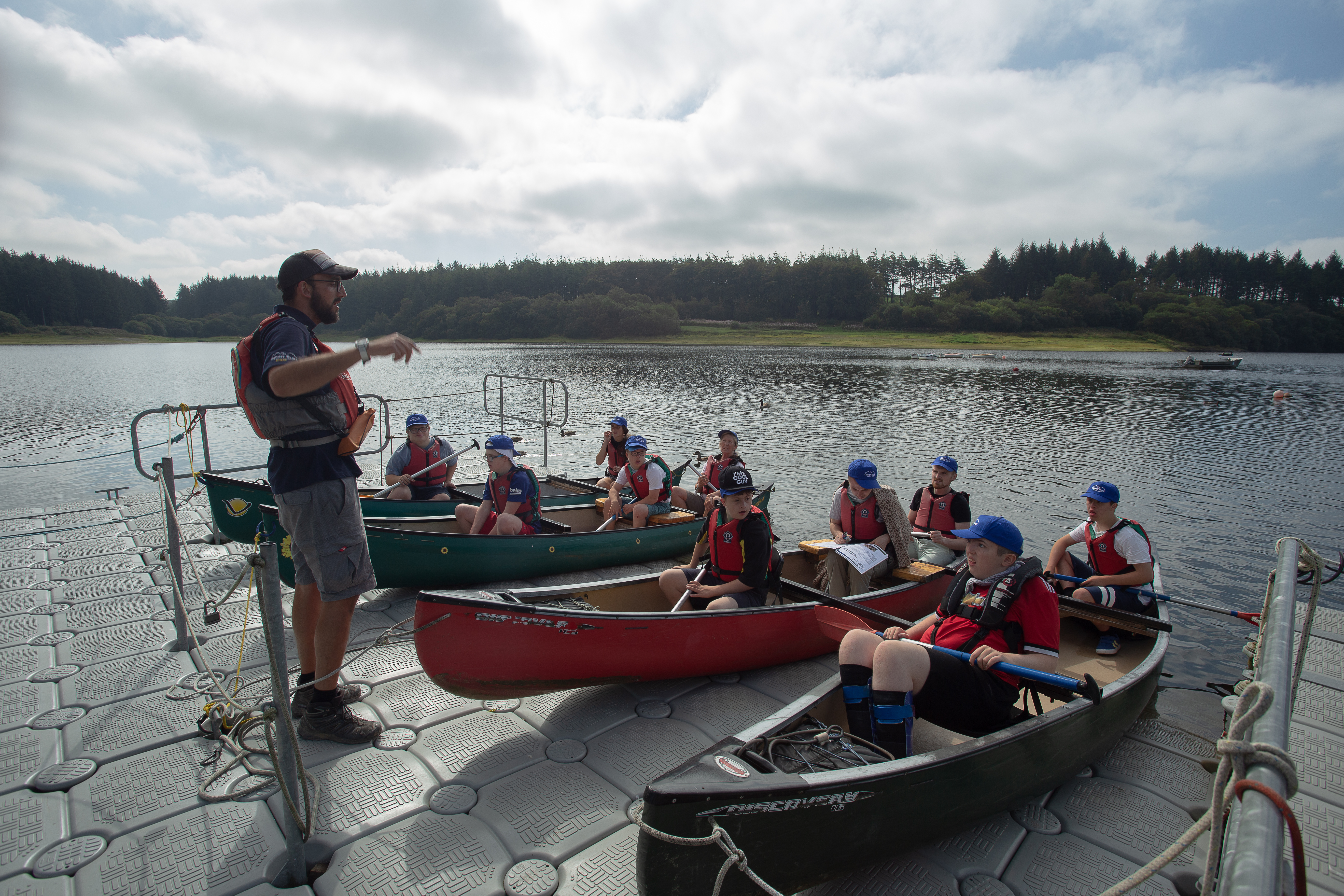 An instructor talking to a group doing canoeing